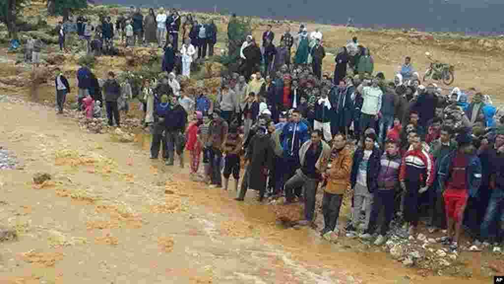Cette image prise avec un téléphone portable montre des habitants de Guelmim, au sud ouest du Maroc, contemplant les eaux de crue, le lundi 24 novembre 2014.