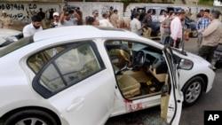 Des enquêteurs et journalistes pakistanais entourent la voiture portant des traces sang du célèbre chanteur soufi Amjad Sabri après l'attaque dont il a été victime à Karachi, au Pakistan, le mercredi 22 juin 2016.