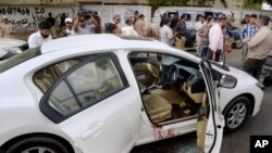 Nhân viên điều tra, nhà báo vây quanh chiếc xe nhuốm máu của ca sĩ nổi tiếng Sufi Amjad Sabri sau khi cuộc tấn công ở Karachi, Pakistan, ngày 22/6/2016.