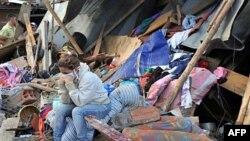 Cư dân ngồi cạnh căn nhà đổ nát sau vụ đất chuồi ở Bello, vùng ngoại ô ở thành phố Medellinnorthwestern của Colombia, ngày 6/12/2010