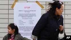 لندن میں ایک خاتون اپنی بچی کے ساتھ سوائن فلو کی وارننگ پوسٹر کے قریب سے گزر رہی ہیں۔