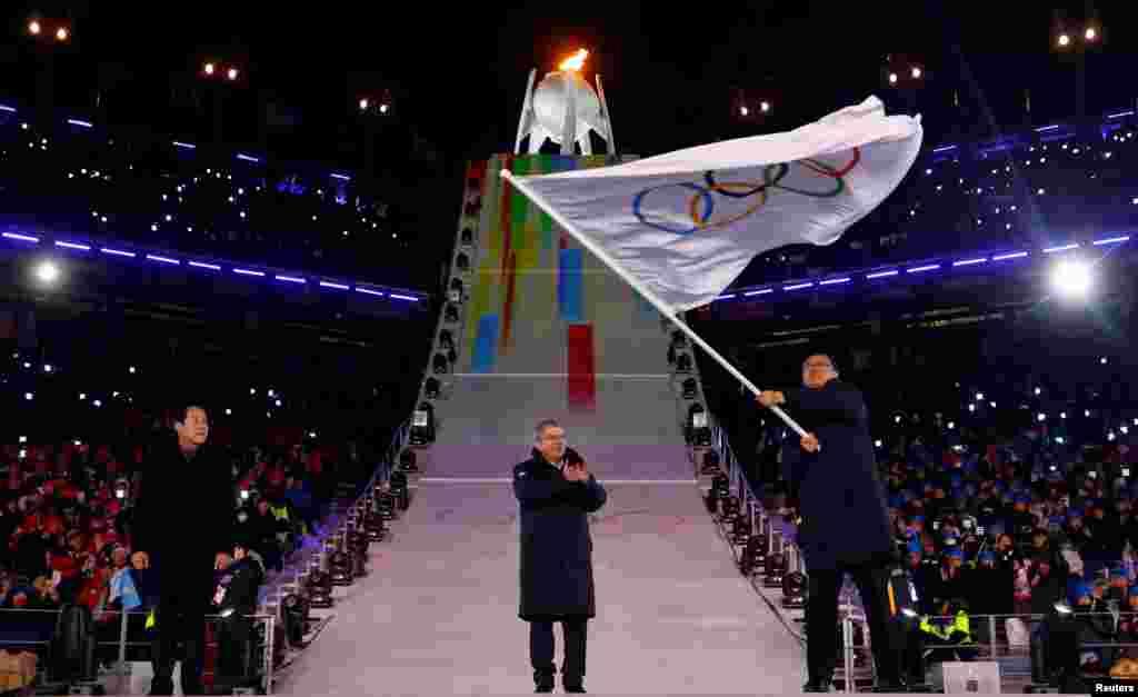 平昌冬奥会闭幕式上,北京市长陈吉宁挥舞奥运旗帜,旁边是国际奥委会主席巴赫和平昌市长。北京将主办2022年冬奥会(2018年2月25日)