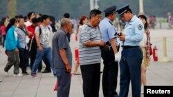 Nhân viên an ninh kiểm tra thẻ căn cước của du khách tại Quảng trường Thiên An Môn ở Bắc Kinh.