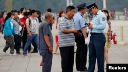 A security officer checks the identification cards of visitors at Tiananmen Square in Beijing, June 4, 2013.