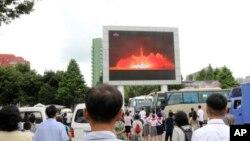 Quelques personnes regardent sur un écran géant le lancement d'un missile à longue portée à Pyongyang, Corée du Nord, 29 juillet 2017.