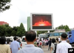 People watch a news broadcast of a missile launch in Pyongyang, North Korea, July 29, 2017. North Korean leader Kim Jong Un said Saturday the second flight test of an intercontinental ballistic missile demonstrated his country can hit the U.S. mainland.