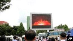 Xelk li Pyongyang, Koreya bakur, roja 29î Tîrmehê 2017 li têsta mûşeka nû mêze dikin.