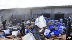 Des soldats dégageant des urnes des décombres d'un magasin incendié le 16 septembre à Conakry