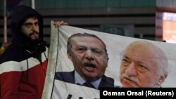 FILE - A demonstrator hold pictures of Turkey's Prime Minister Tayyip Erdogan and Turkish cleric Fethullah Gulen (R), during a protest in Istanbul Dec. 30, 2013.