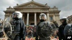 Polisi Anti Huru-hara mengenakan pakaian pelindung dalam peringatan untuk para korban serangan di Brussels dekat Place de la Bourse, Brussels (27/3).