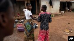 Marie walks with a friend on a street in Komao village, on the outskirts of Koidu, district of Kono, Sierra Leone, Sunday, Nov. 22, 2020. (AP Photo/Leo Correa)