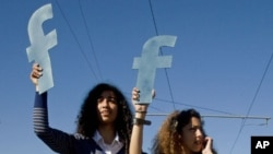 "Protesters hold ""f""s in recognition of social network site Facebook's role in the North African revolts, during a protest by thousands over civil rights, in Rabat, Morocco, March 2011."