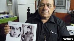 Raul Borges, 74, memegang foto anaknya Ernesto Borges di rumahnya di Havana (2/1). Ernesto telah dipenjara di Kuba selama 16 tahun setelah mencoba membocorkan rahasia ke seorang diplomat AS di Kuba.
