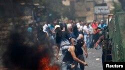 Một người Palestine ném đá vào cảnh sát Israel trong cuộc đụng độ giữa người biểu tình và cảnh sát ở Đông Jerusalem, 25/7/14