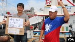 """台灣屏東漁民發起的""""保祖產護主權""""活動發言人羅強飛與一名參與者展示台中網友寄來的以青天白日旗為圖案的T卹。"""