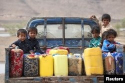 FILE - Children ride on the back of a truck loaded with water jerrycans at a camp for internally displaced people in the Dhanah area of the central province of Marib, Yemen, April 30, 2016.