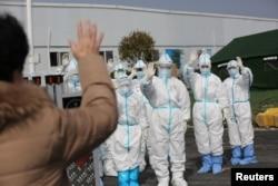 身穿防护服的武汉医务人员挥手送别康复出院的新冠病毒患者。(2020年3月1日)