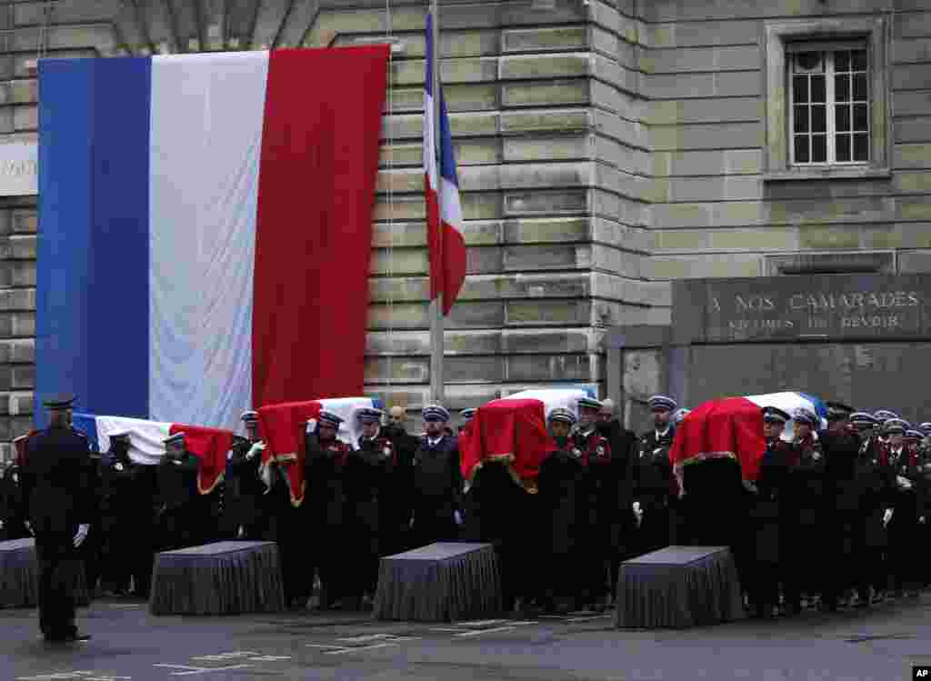 Police officers carry the coffins of the four victims of last week's knife attack during a ceremony in the courtyard of the Paris police headquarters. France's presidency said the victims will be posthumously given the country's highest award, the Legion of Honor.