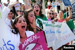 FILE - Anti-abortion demonstrators cheer as the ruling for Hobby Lobby regarding contraceptives coverage was announced outside the U.S. Supreme Court in Washington, June 30, 2014.