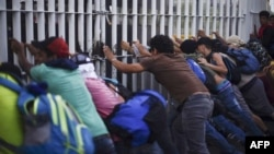 Honduran migrants taking part in a caravan heading to the US, tear down the border fence between Ciudad Tecun Uman in Guatemala and Ciudad Hidalgo, Mexico, Oct. 28, 2018.