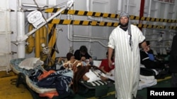 Injured men rest inside a Turkish ship carrying 250 wounded people from the besieged Libyan city of Misrata, at a port in Benghazi, Apr 3 2011.