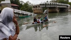 FILE - Villagers ride on a boat to cross a river after bridge was damaged in Loon, Bohol, Oct. 16, 2013, a day after an earthquake hit central Philippines.