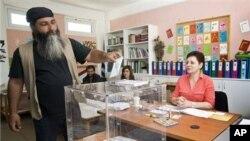 Seorang warga Yunani memasukkan surat suaranya saat Pemilu 6 Mei yang gagal memilih pemenang. Pemilu ulang akan dilaksanakan lagi bulan depan
