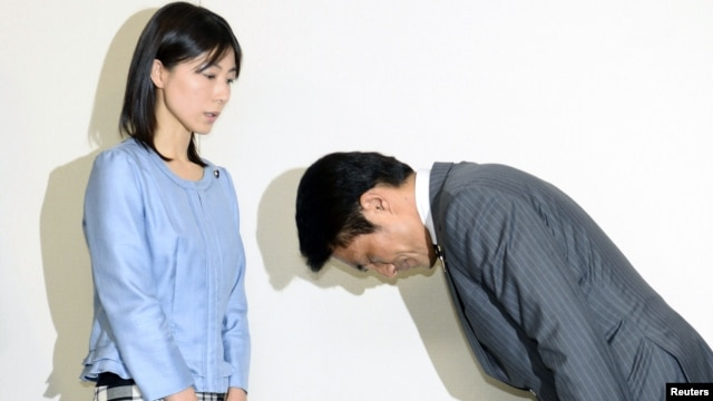 Tokyo city assembly lawmaker Akihiro Suzuki (R) bows to apologize to female lawmaker Ayaka Shiomura at Tokyo Metropolitan City Hall, in this photo taken by Kyodo, June 23, 2014.