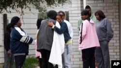 Familiares y amigos de las víctimas se consuelan mutuamente el domingo, luego que se produjera la trágica fiesta de 18 años que terminó con la vida de dos estudiantes en Cypress, Texas.