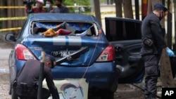 Anggota polisi penjinak bom memeriksa area sekitar lokasi serangan bom bunuh diri hari Minggu di Katedral Hati Kudus Yesus di Makassar, Sulawesi Selatan, Senin, 29 Maret 2021. (Foto: AP)