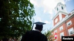 Seorang lulusan Harvard University bersiap mengikuti upacara kelulusan di kampus tersebut.