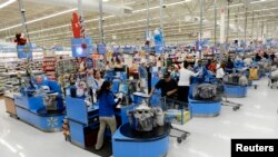 FILE - Cashiers work checkout lanes of a Walmart store in the Porter Ranch section of Los Angeles, California.