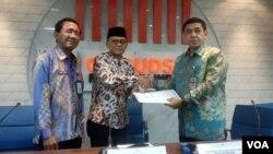 Anggota Ombudsman RI Ahmad Suaedy memberikan laporan temuan Ombudsman ke Asisten Deputi Koordinator Pemajuan dan Perlindungan HAM Kemenko Polhukam Rudy Syamsir di kantor Ombudsman, Jakarta, Kamis (5/12). (Foto: VOA/Sasmito)