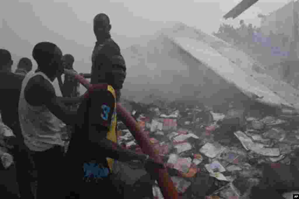 Rescue workers search for survivals at the site of a Dana Airlines passenger plane crash in Lagos, Nigeria, Sunday, June 3, 2012.