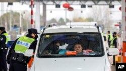 Polisi China menggunakan termometer memeriksa suhu tubuh seoran pengendara di kota Wuhan (23/1).