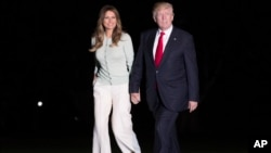 President Donald Trump and first lady Melania Trump walk from Marine One across the South Lawn to the White House in Washington, May 27, 2017, as they return from Sigonella, Italy.