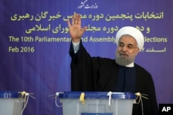 FILE - President Hassan Rouhani waves to media after casting his vote in Tehran, Iran, Feb. 26, 2016. The moderate leader and his allies won 15 out of Tehran's 16 seats in the election for the Assembly of Experts.