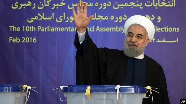 In this photo released by official website of the office of the Iranian Presidency, President Hassan Rouhani waves to media after casting his vote for parliamentary and Experts Assembly elections in Tehran, Iran, Feb. 26, 2016.