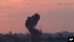 FILE - Smoke rises after an Israeli missile strike in the Gaza strip as seen from the Israel Gaza border, July 16, 2014.