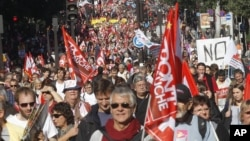 Demonstrators march during a rally with banners and flags to protest against the austerity measures announced by the French government, in Paris, Sunday, Sept 30, 2012.