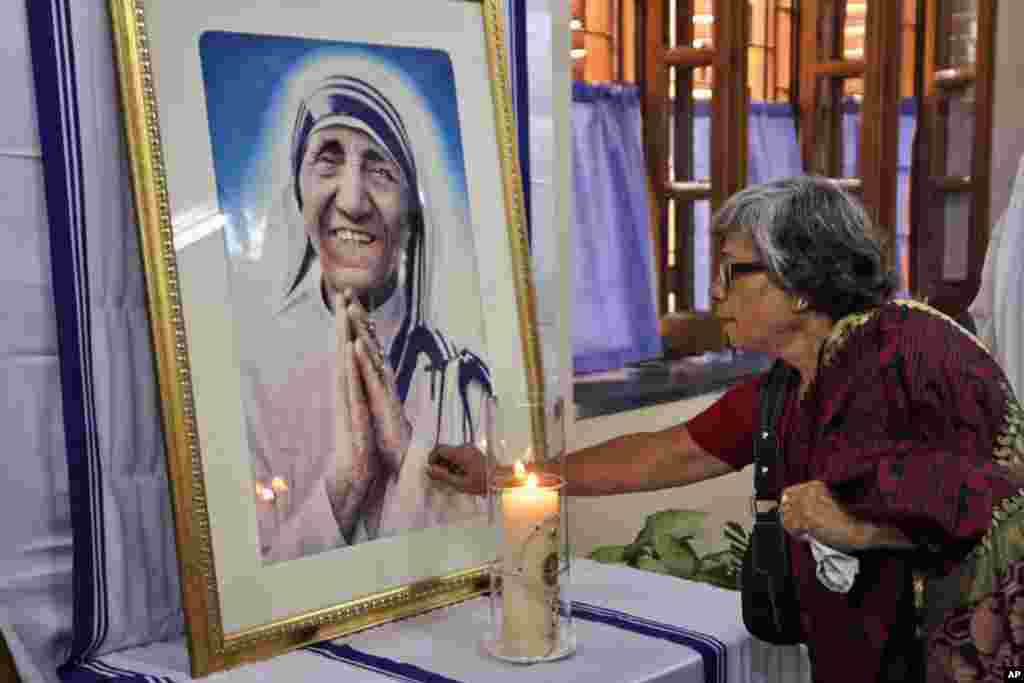 An Indian Catholic woman offers prayers as she touches a portrait of Mother Teresa on the 17th anniversary of her death at the Missionaries of Charity in Kolkata, India.