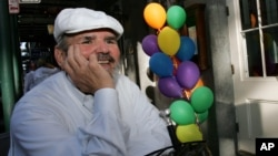 FILE - Chef Paul Prudhomme sits in front of his restaurant 'K-Paul's Louisiana Kitchen' in the French Quarter, in New Orleans, Louisiana, Oct. 18, 2005.