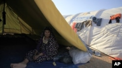 A Libyan refugee who fled unrest in Libya sit inside her tent at a refugee camp near the southern Libyan and Tunisian border crossing of Dehiba May 8, 2011.