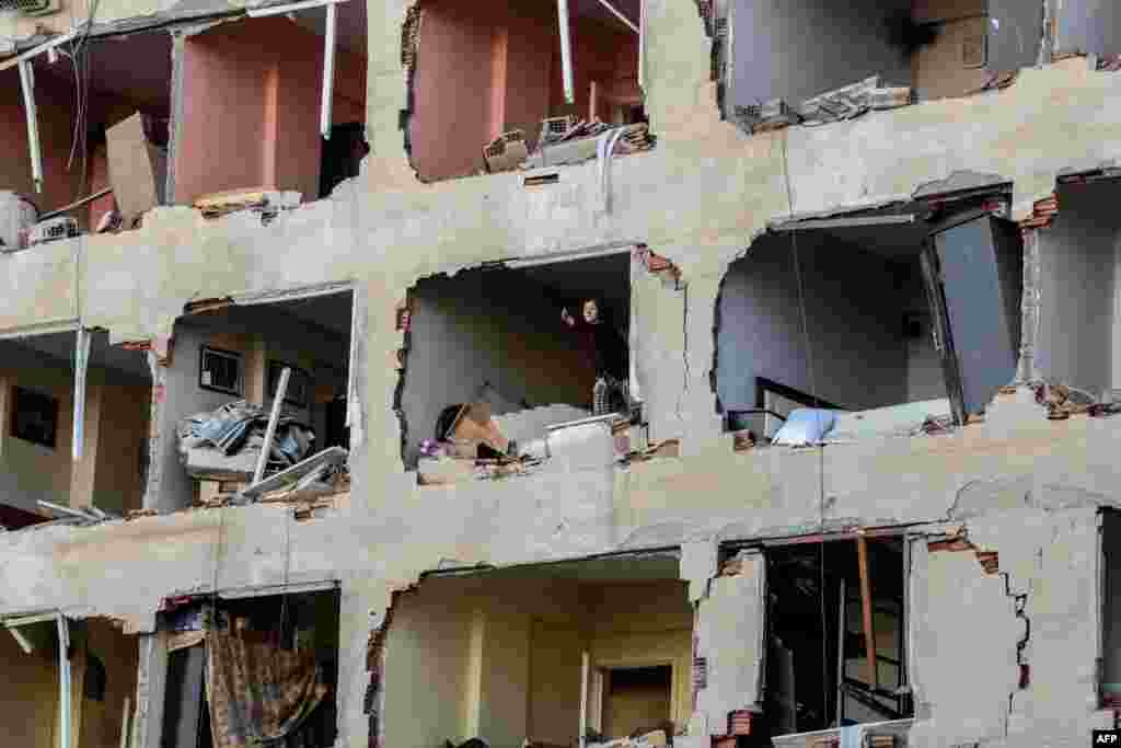 A woman reacts in her damaged apartment on the explosion site, after a strong blast in the southeastern Turkish city of Diyarbakir. At least one person was killed and 30 injured in a blast outside a police building.