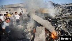 Cư dân tụ tập cạnh đống đổ nát sau một cuộc không kích của Israel ở Rafah ở miền nam Dải Gaza, ngày 20/8/2014.
