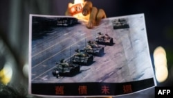 """在香港维多利亚公园参加纪念六四事件31周年的一名男子手持天安门广场""""坦克人""""的照片。(2020年6月4日)"""