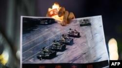 """香港抗议如火如荼之时,美国也发生大规模抗议活动。图为在局势动荡的香港,人们仍然为六四举哀:香港维多利亚公园纪念六四事件31周年的一名男子手持天安门广场""""坦克人""""的照片。(法新社2020年6月4日资料照)"""