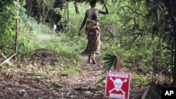 FILE - A woman enters a forest area along a path that has been cleared of landmines, in Orientale Province in the Democratic Republic of Congo.