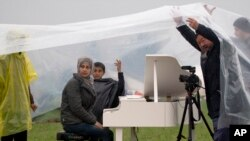 Pembangkang China Ai Weiwei (kanan) menaungi pemain piano Suriah, Nour Alkhzam di tengah hujan deras di Idomeni, Yunani (12/3). (AP/Vadim Ghirda)