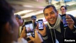 Seorang pembeli menunjukkan iPhone 6 dan iPhone 6 Plus pada hari pertama penjualan model baru iPhone di toko Apple di Manhattan, New York, September lalu.